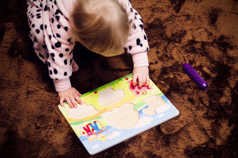 baby girl solving jigsaw