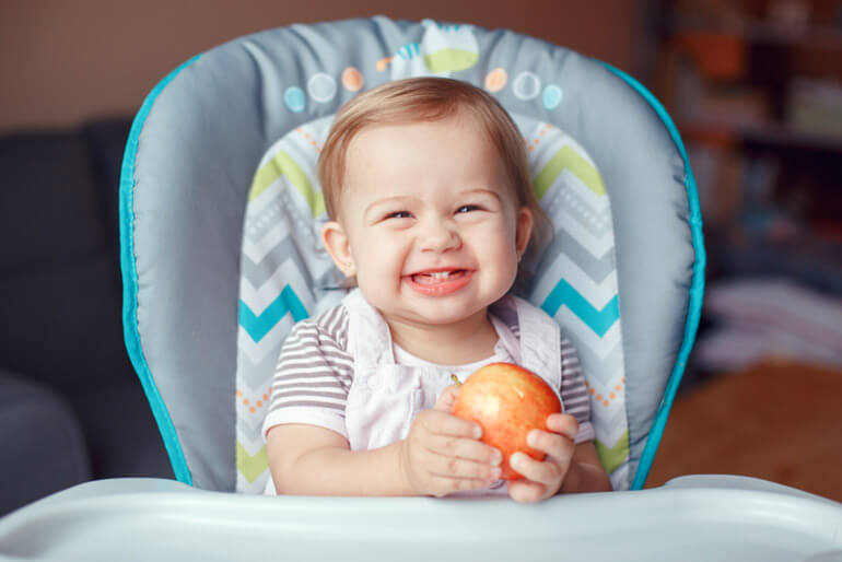 baby on high chair eating apple