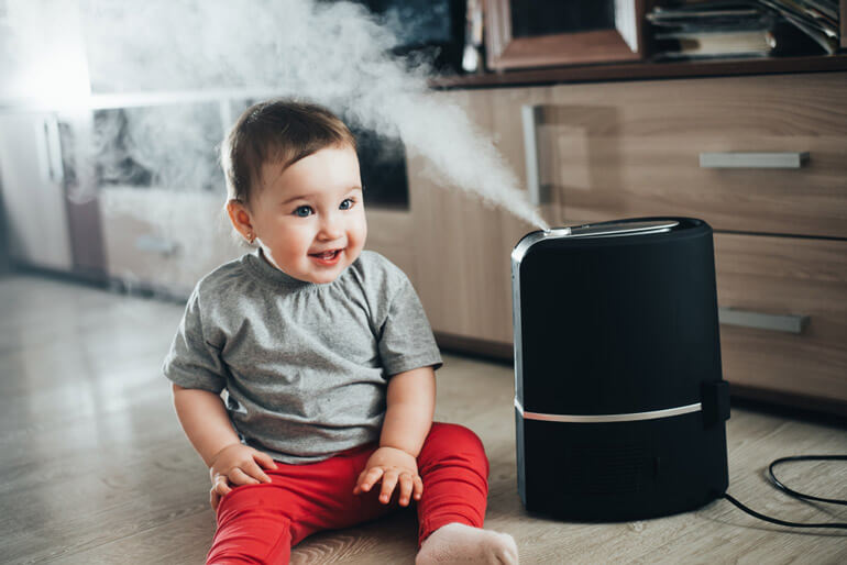 baby playing with humidifier