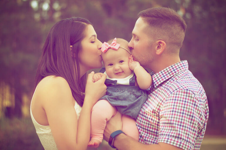 parents kissing their baby girl
