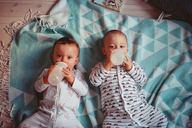 twins drinking from bottles