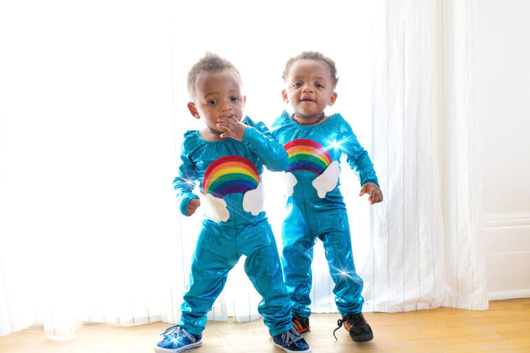 twins sparkling in rainbow costumes